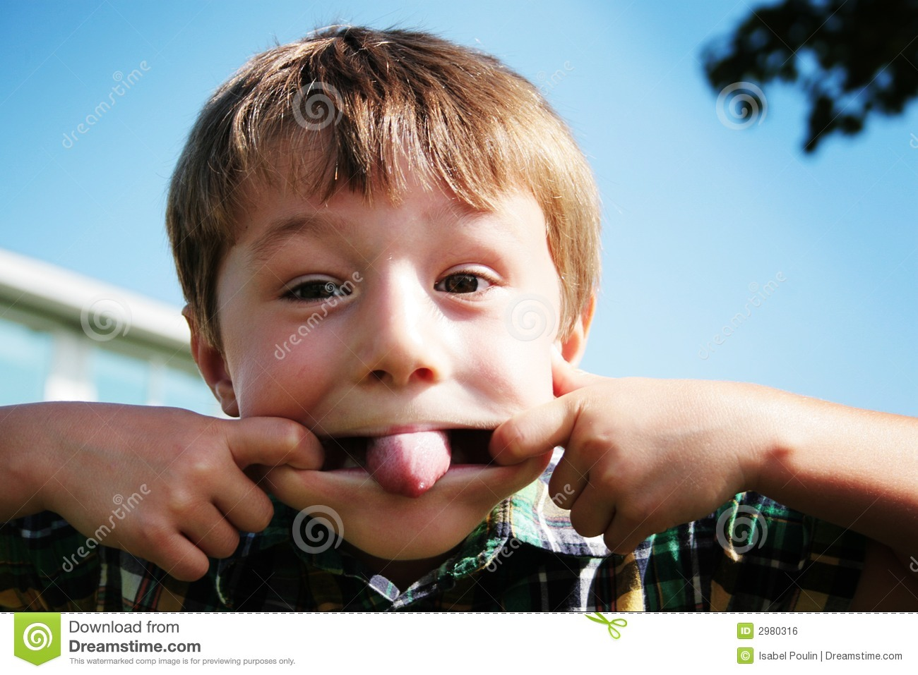 portrait of a young boy making a funny face by stretching his mouth