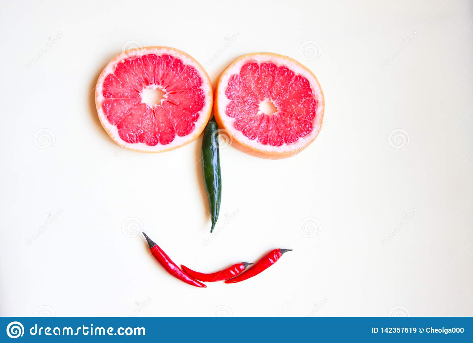 Funny face made of fruit and colored hot pepper