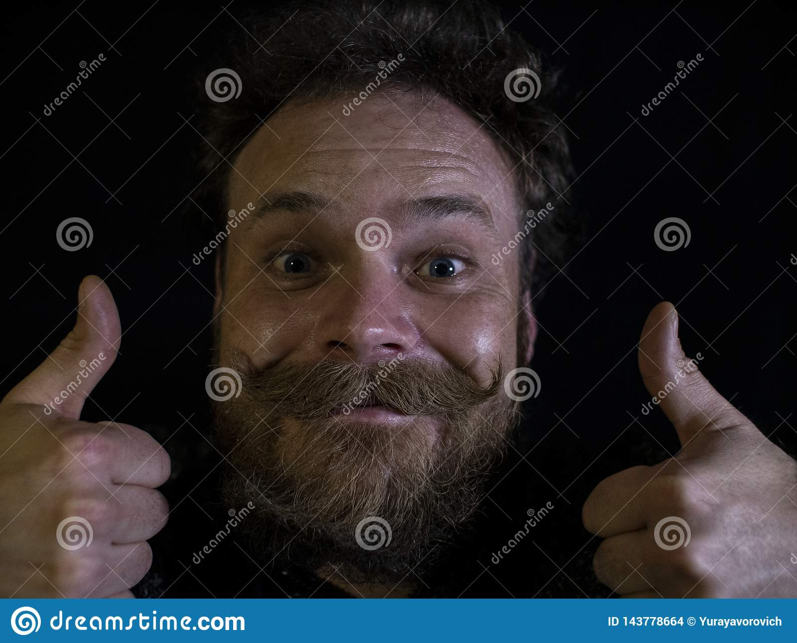 Funny face of a man with a beard and mustache close up and showing thumbs up