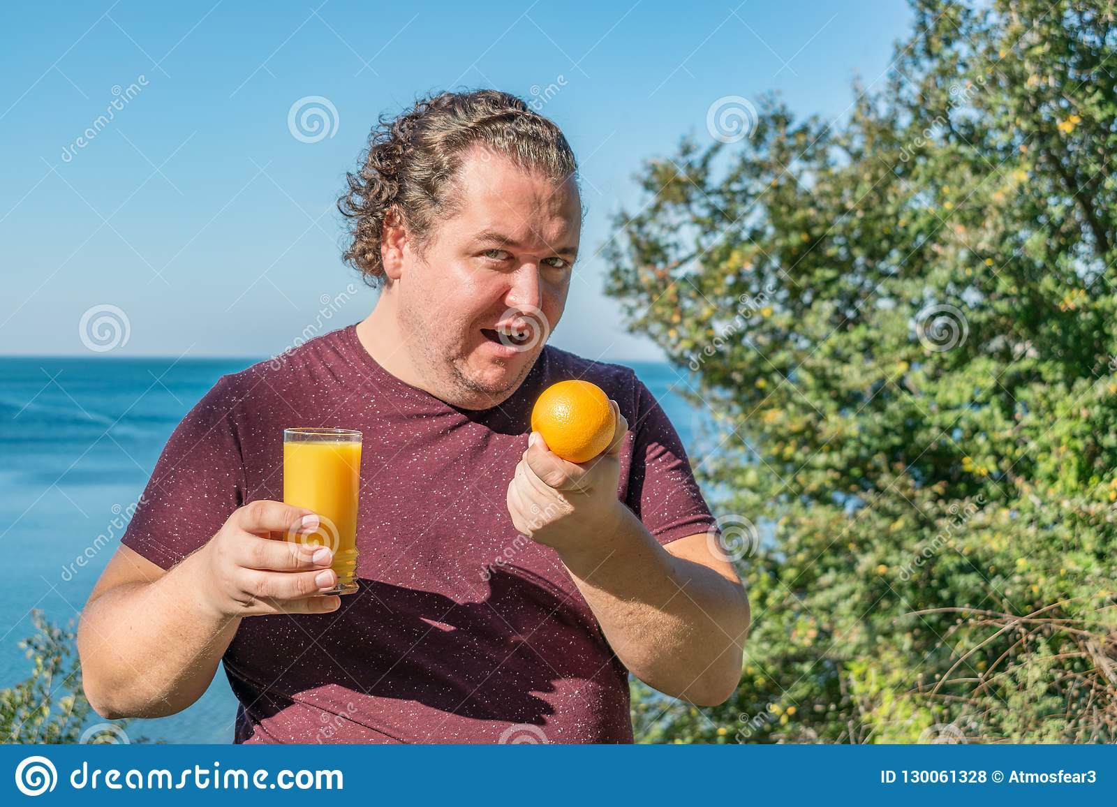 Funny fat man on the ocean drinking juice and eating fruits. Vacation, weight loss and healthy eating