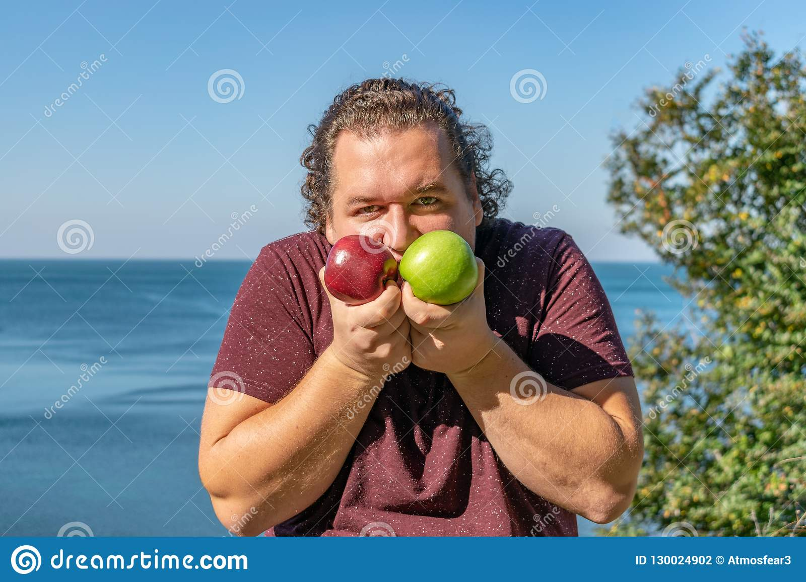 Funny fat man on the ocean eating fruits. Vacation, weight loss and healthy eating