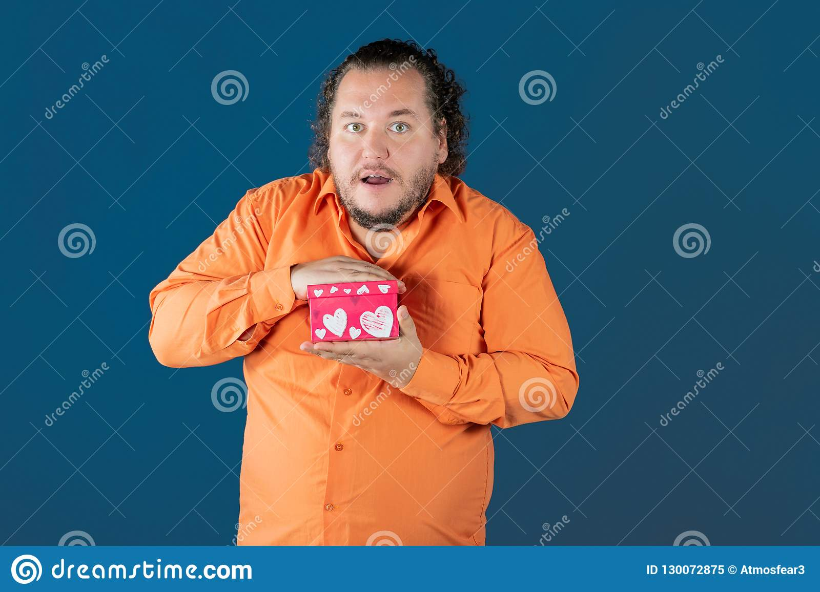 Funny fat man in orange shirt opens a box with a gift