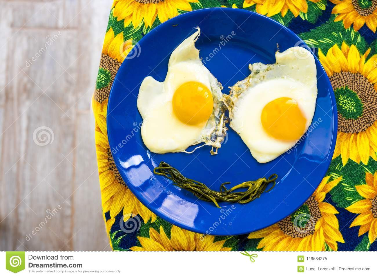 Funny food face smile fried eggs eyes vegetable mouth blue dish