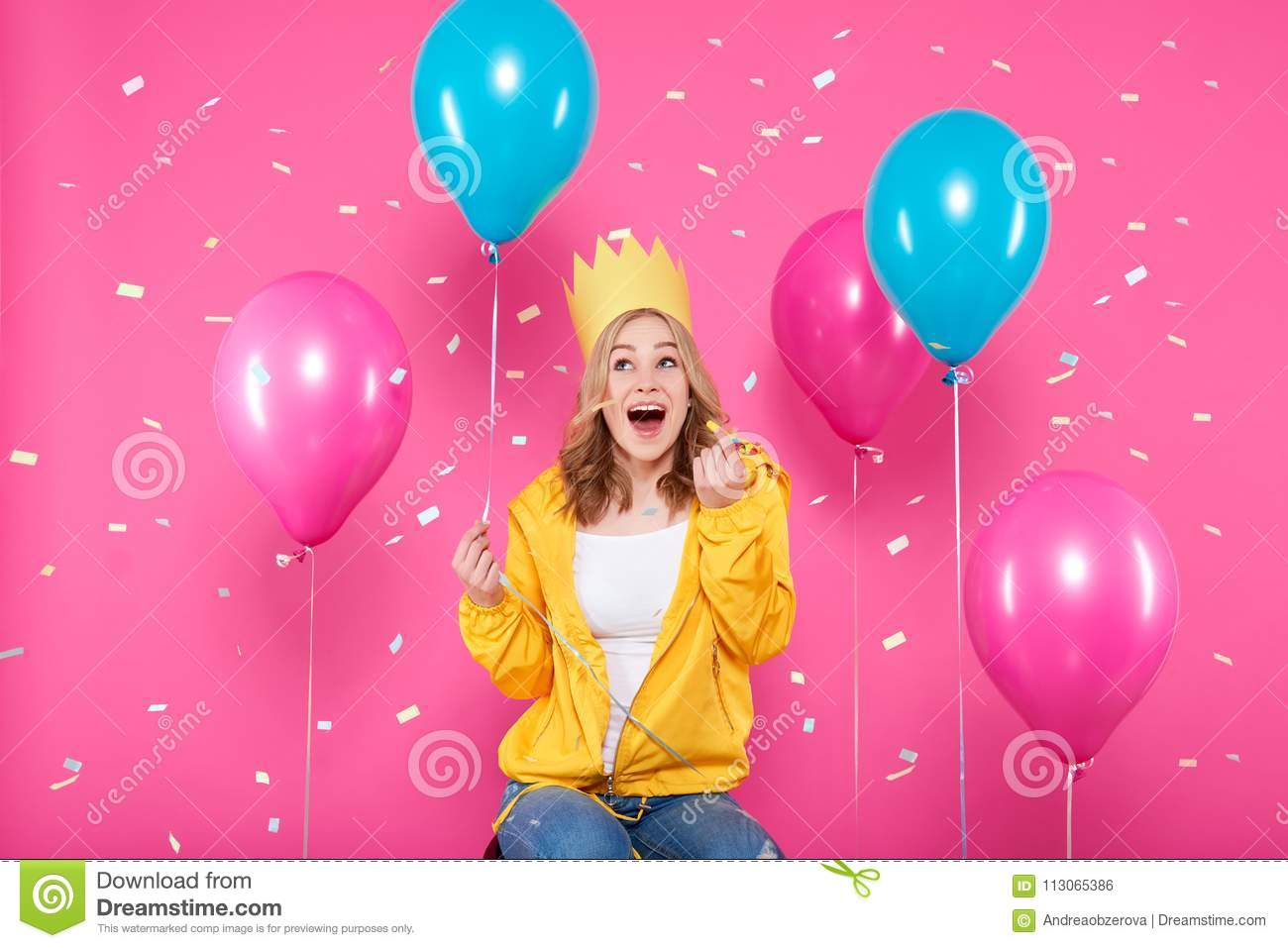 Funny girl in birthday hat, balloons and flying confetti on pastel pink background. Attractive teenager celebrating birthday.