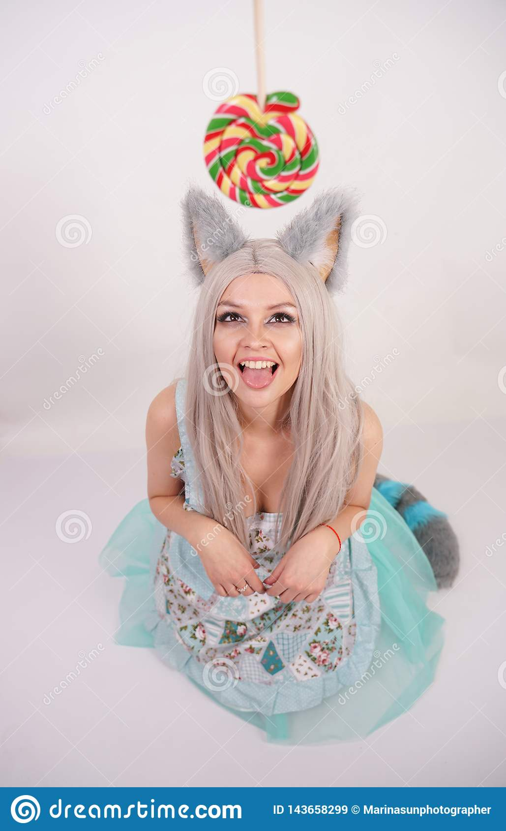 Funny girl with fluffy fur cat ears stands in a kitchen apron on knees and serves as a slavery kitty to get candy on a white backg