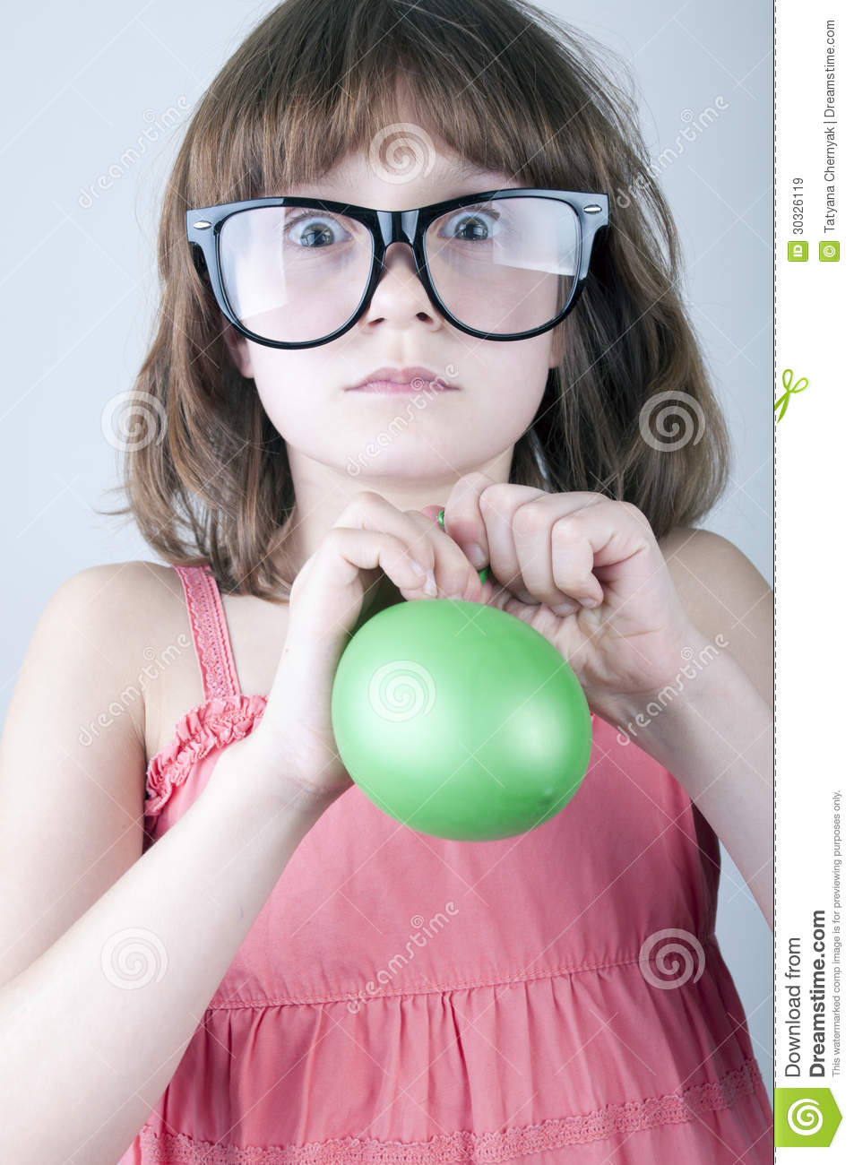 Funny girl with herd sunglasses blowing a balloon