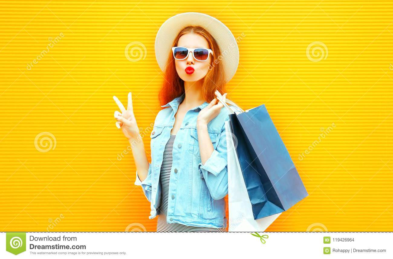 Funny girl makes an air kiss holds a shopping bags in straw hat