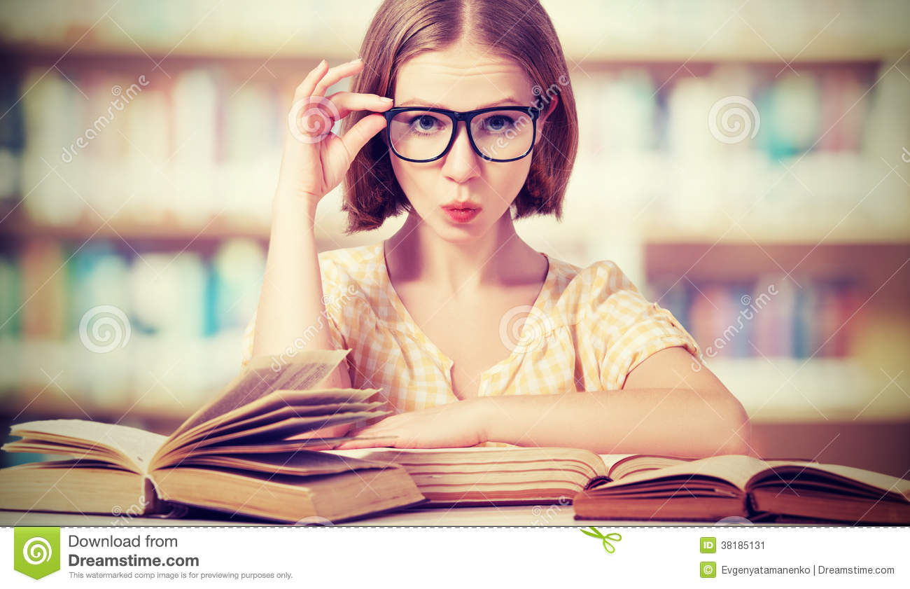 Funny girl student with glasses reading books