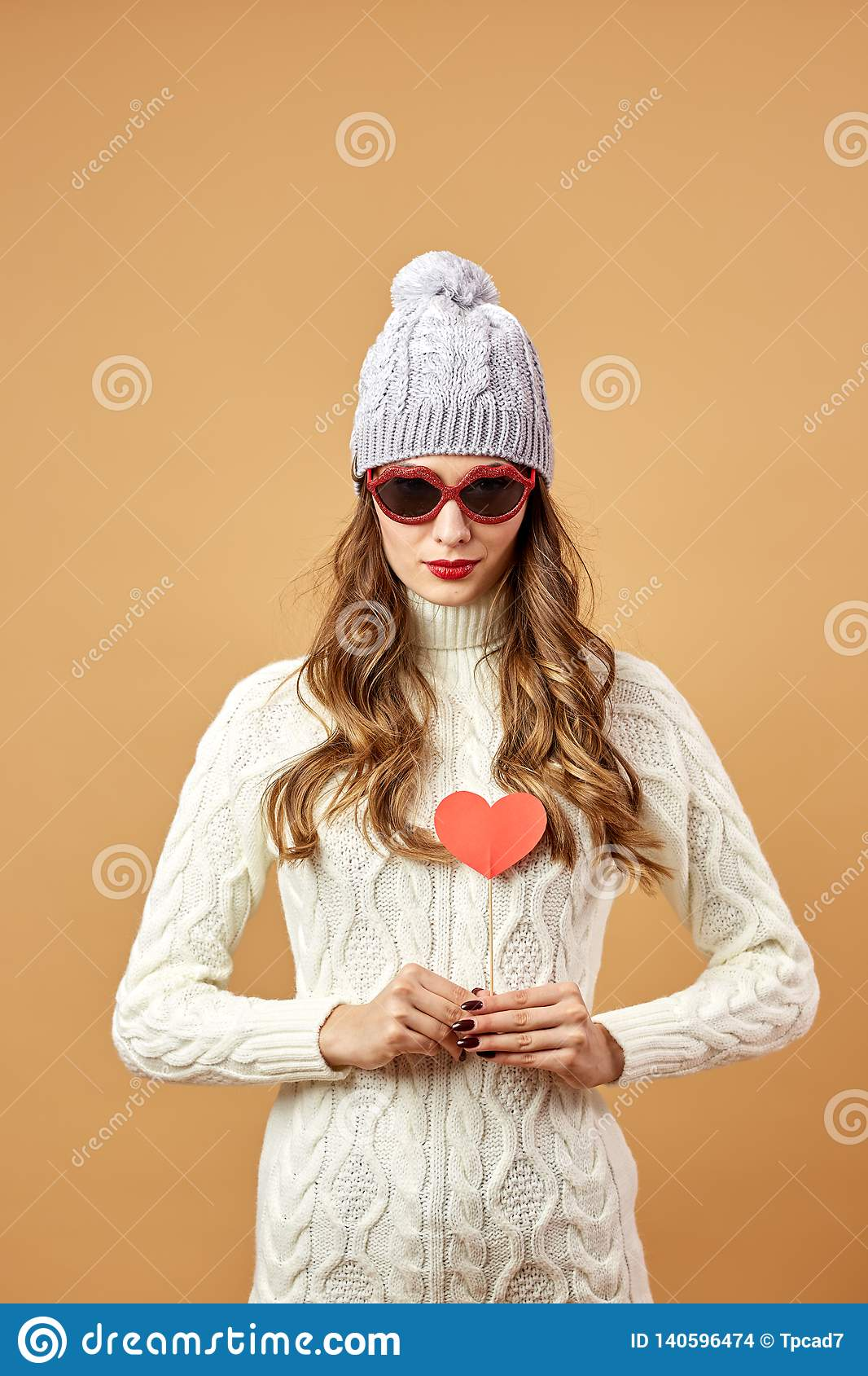 fc34b6118f4 Funny girl in sunglasses dressed in white knitted sweater and hat haves fun  with a red paper heart on a stick on a beige background in the studio .