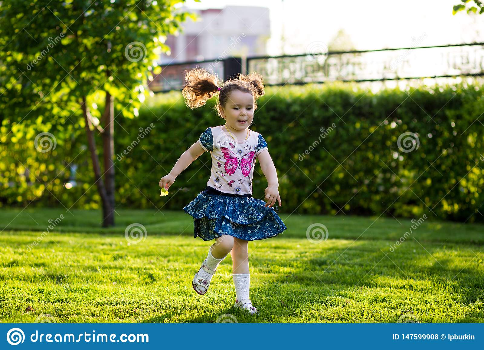 Funny girls walking on the lawn with her mother. Sisters play together with mom. maternal care. happy family