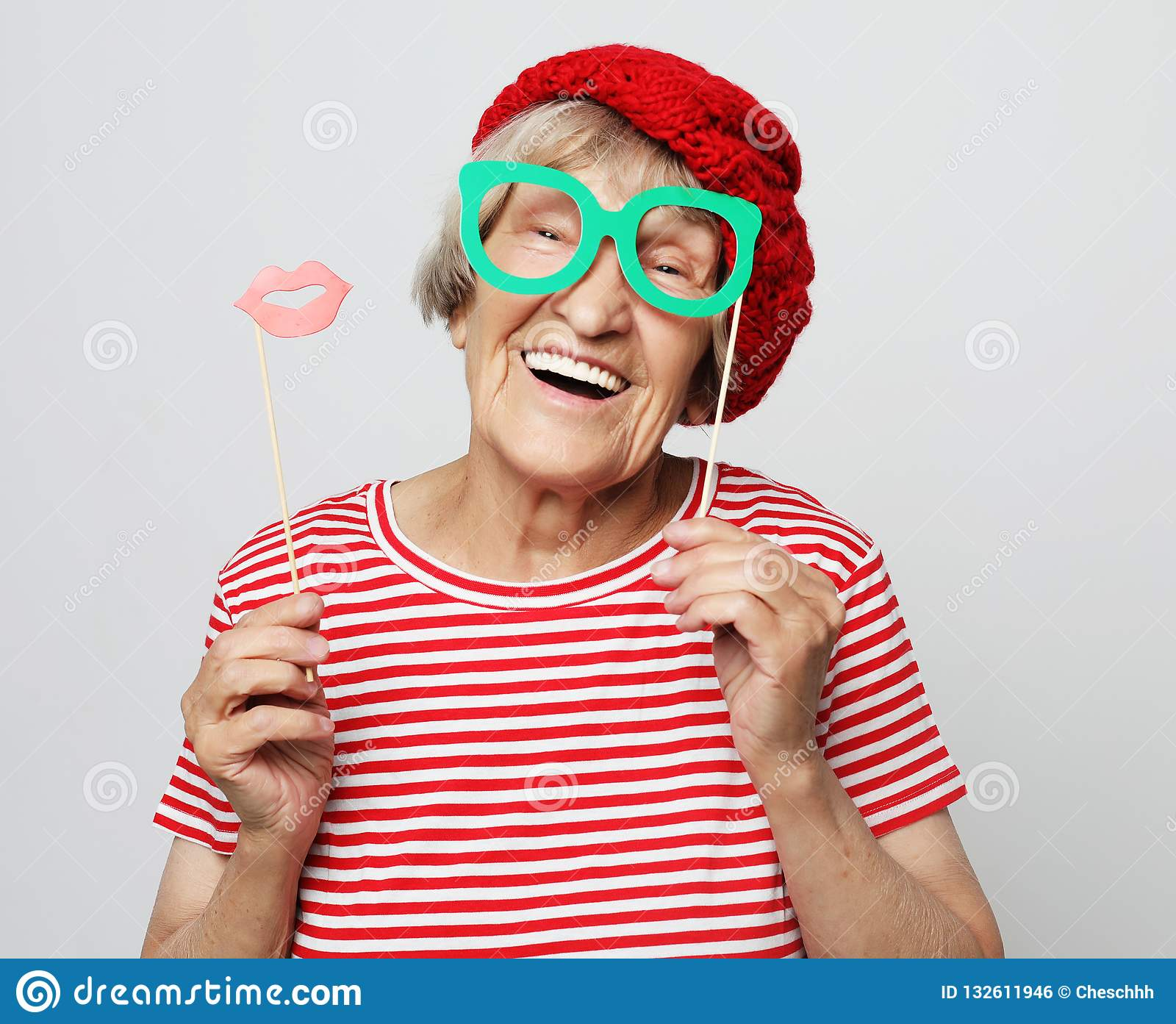 Funny grandmother wearing red clothes holding falce glasses and ready for party