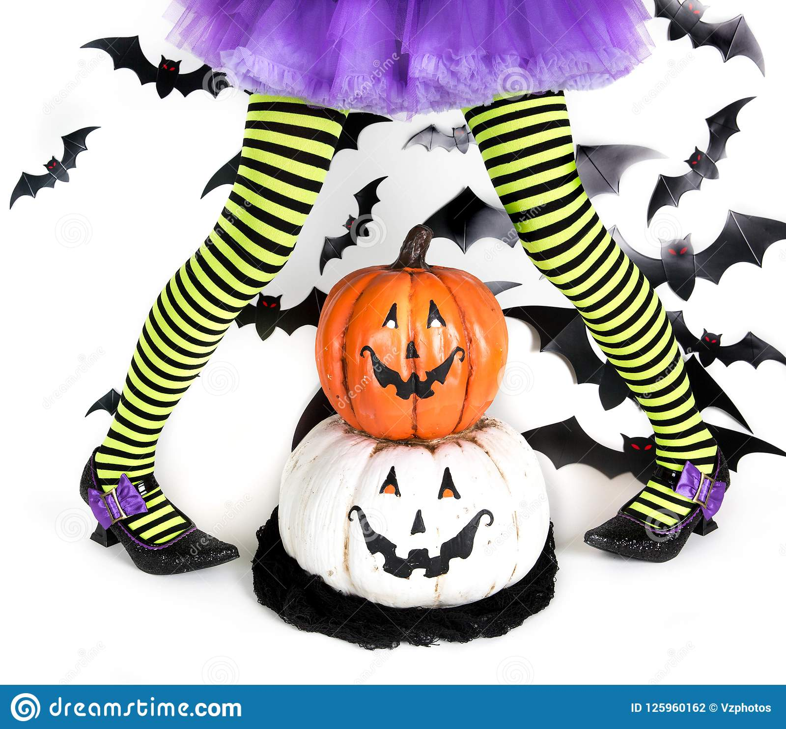 Funny green black Striped legs of a little girl with halloween costume of a witch with witch shoes and smiley halloween pumpkin