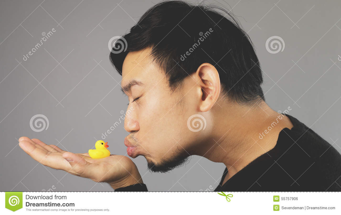 A funny guy kissing his rubber duck.