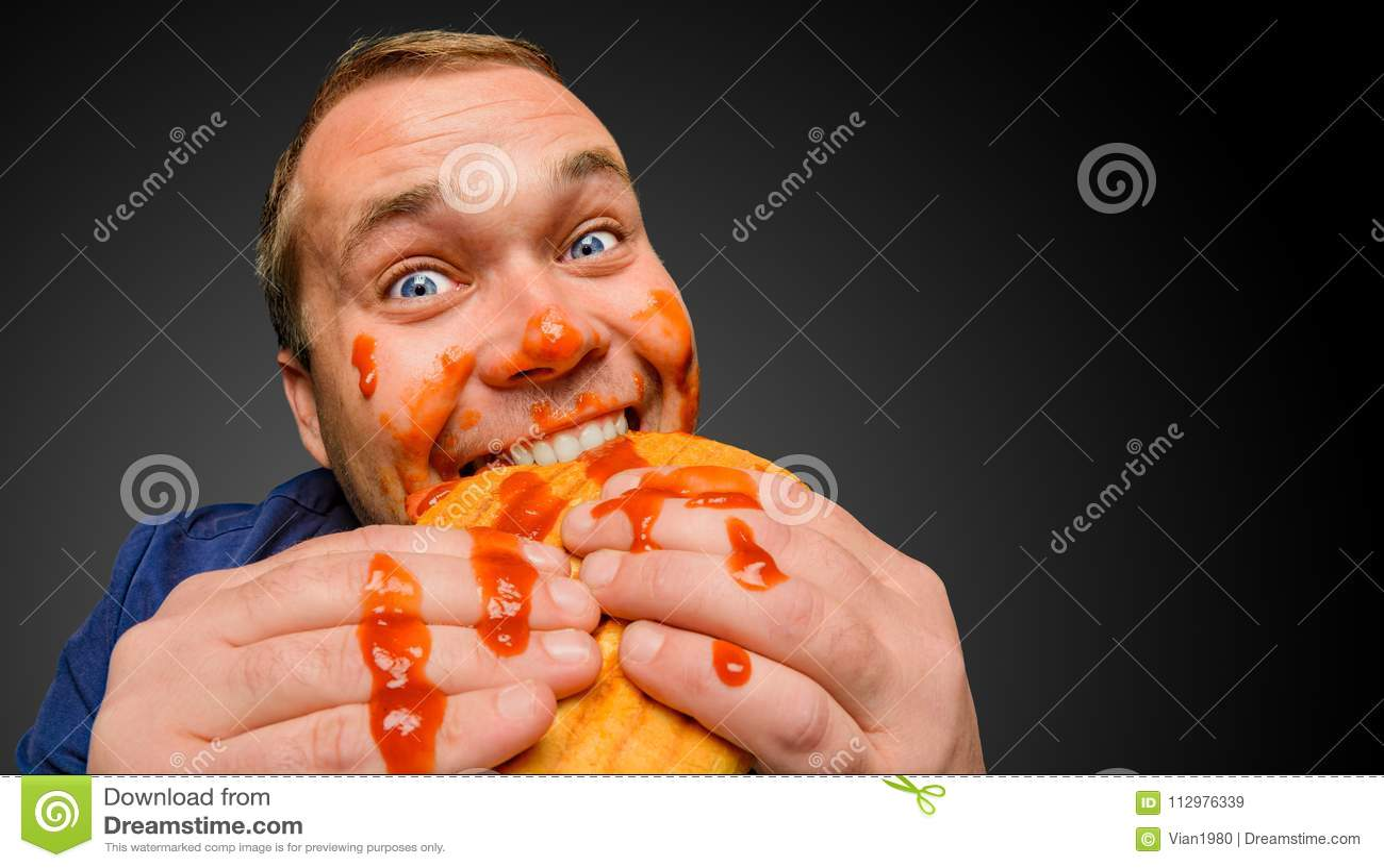Fat man bites the tasty panini sandwich
