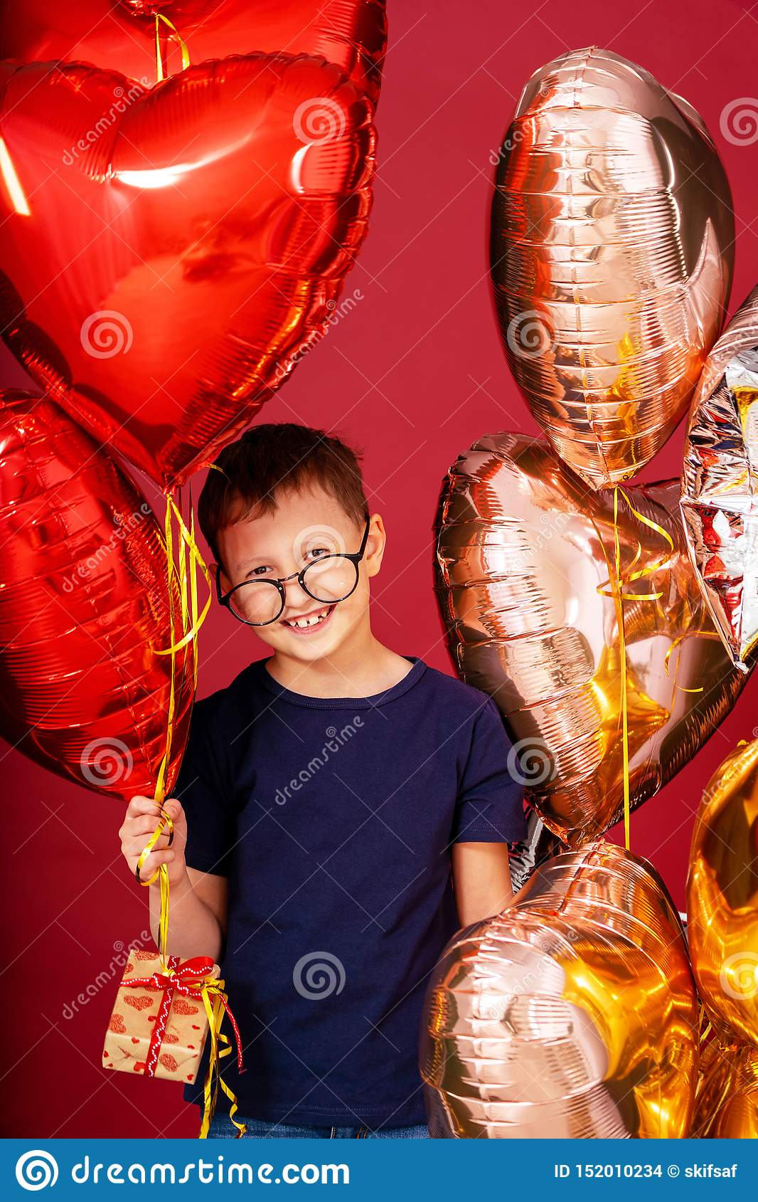 Funny kid boy in glasses, different color heart, star balloons for valentines day or birthday on red background with free text