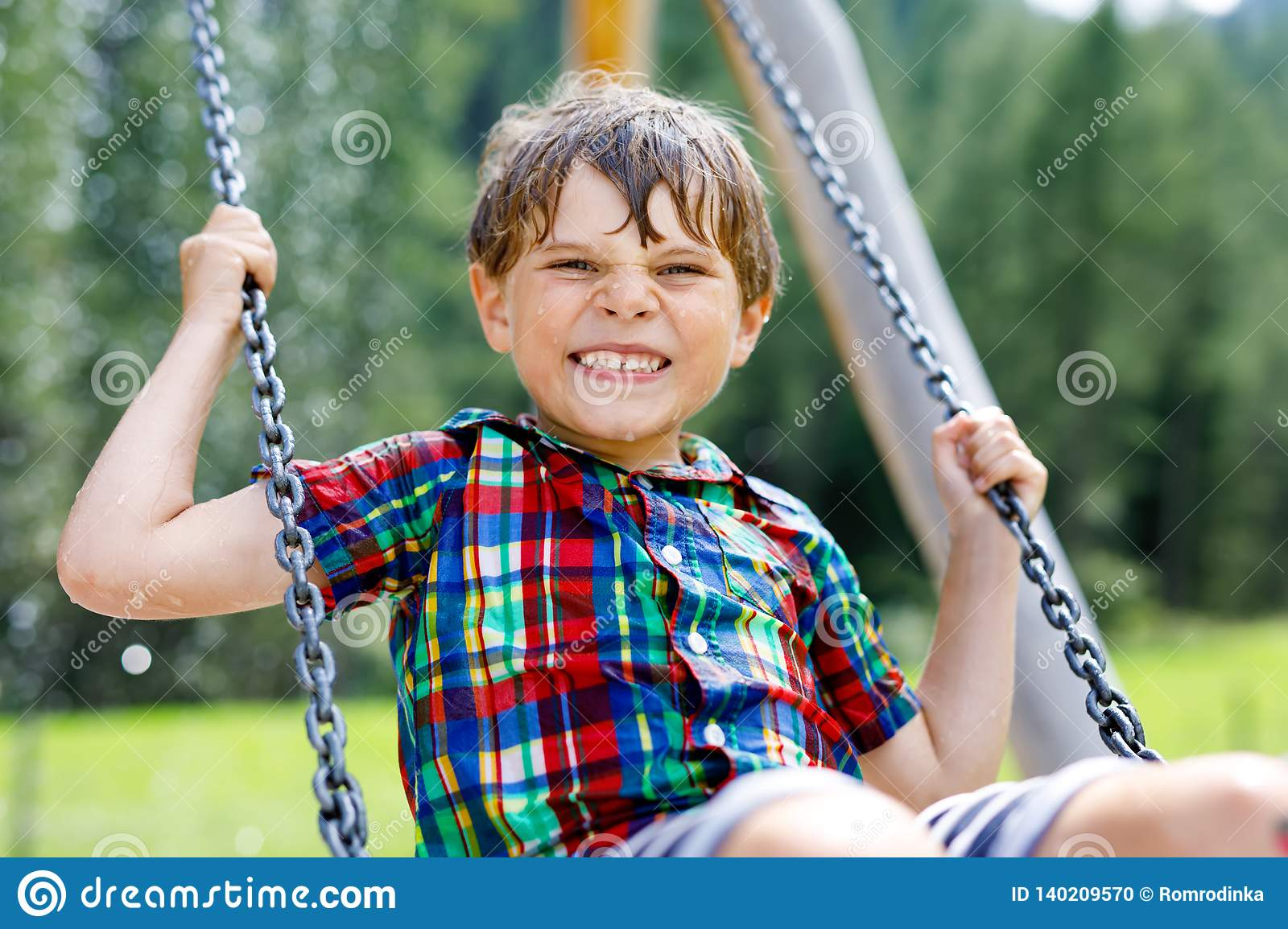 Funny kid boy having fun with chain swing on outdoor playground while being wet splashed with water. child swinging on
