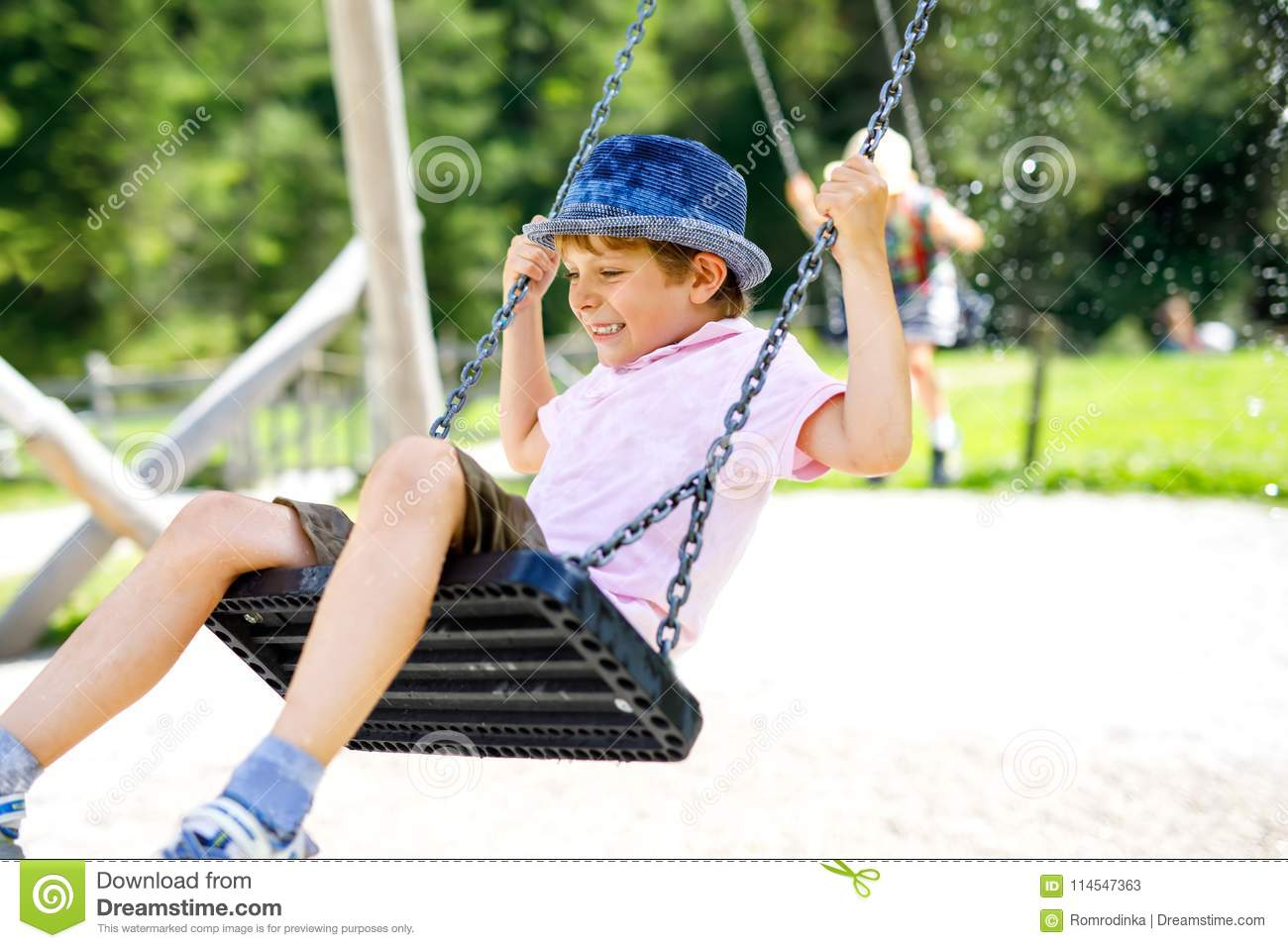 Funny kid boy having fun with chain swing on outdoor playground while being wet splashed with water