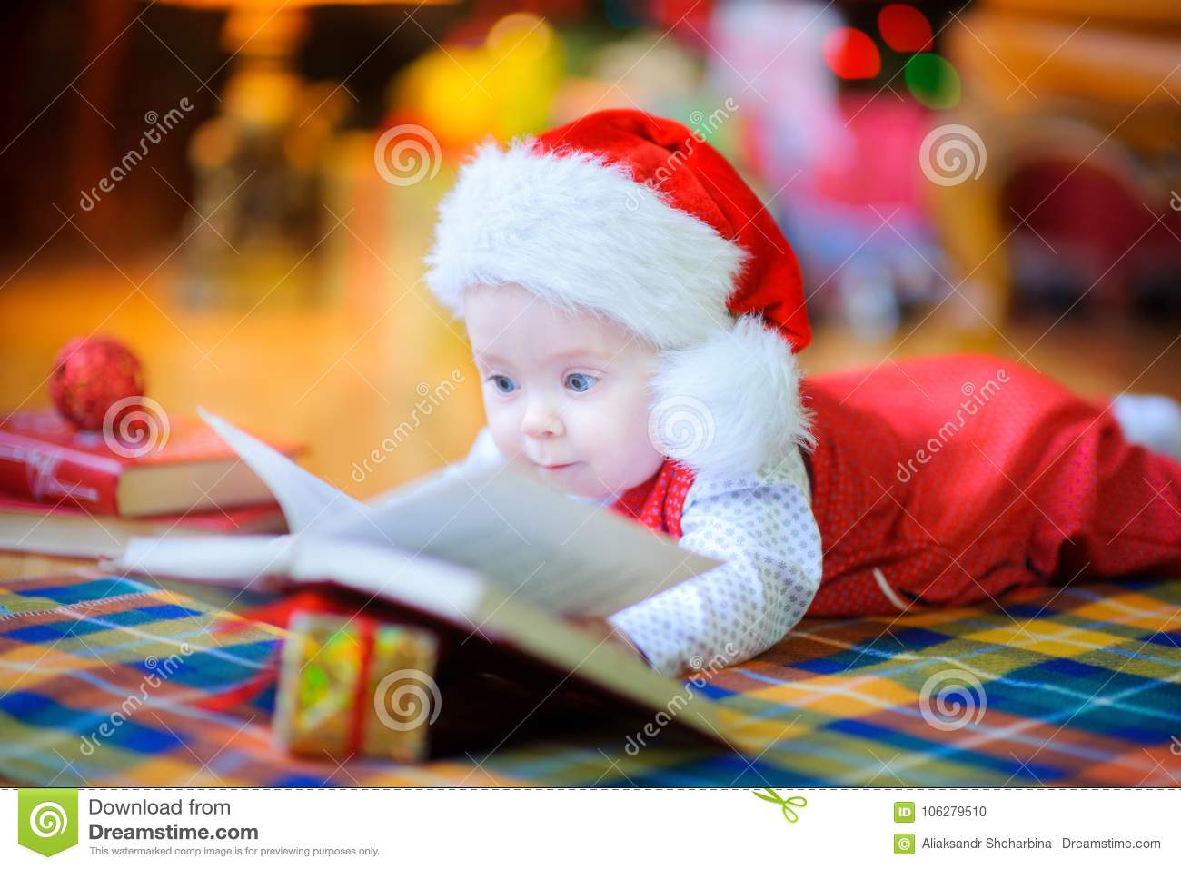 9bfd4b9348 A funny kid in a Santa Claus hat lies on the floor near the Christmas tree  and reads a book