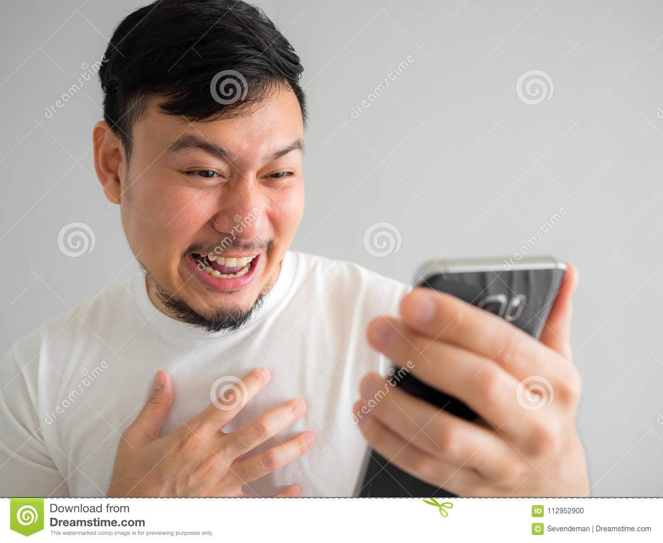 Funny laugh face of man watching funny video clip share in social in the smartphone.