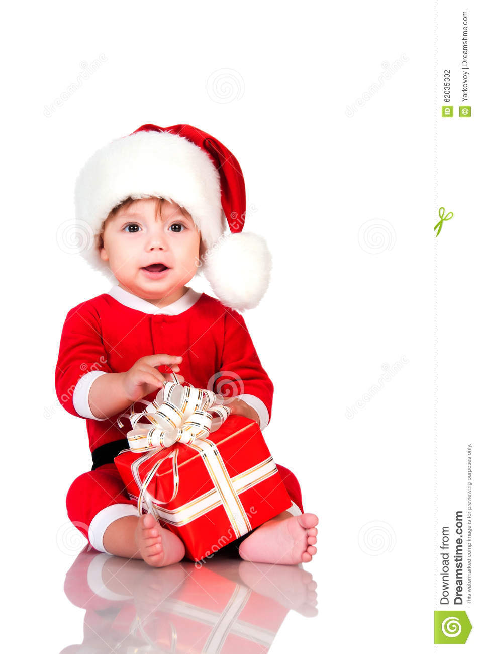 Funny little boy in Santa Claus suit with gift boxes. Happy New Year and christmas holidays