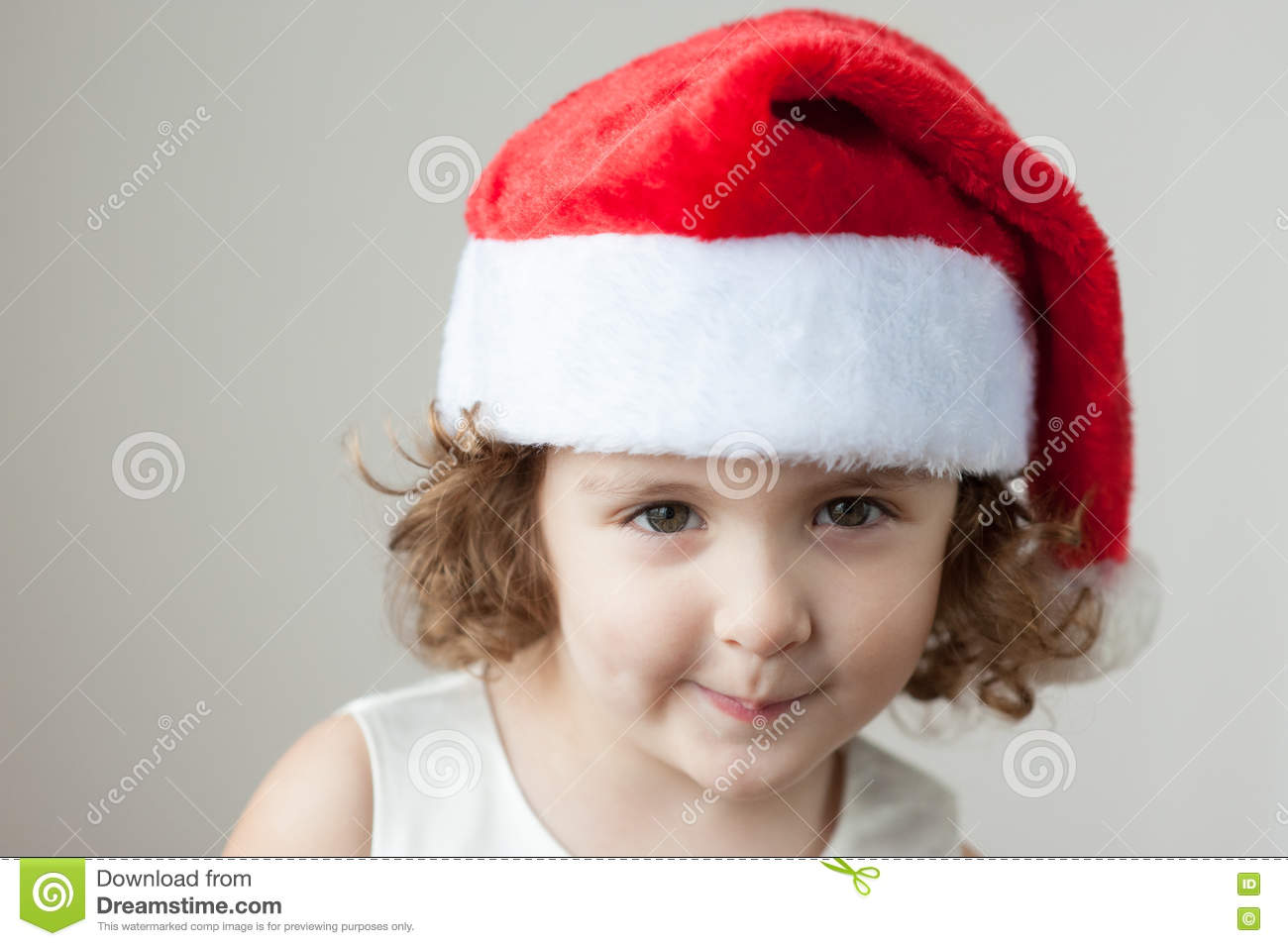 Funny little curly blonde girl in a santa hat stock image