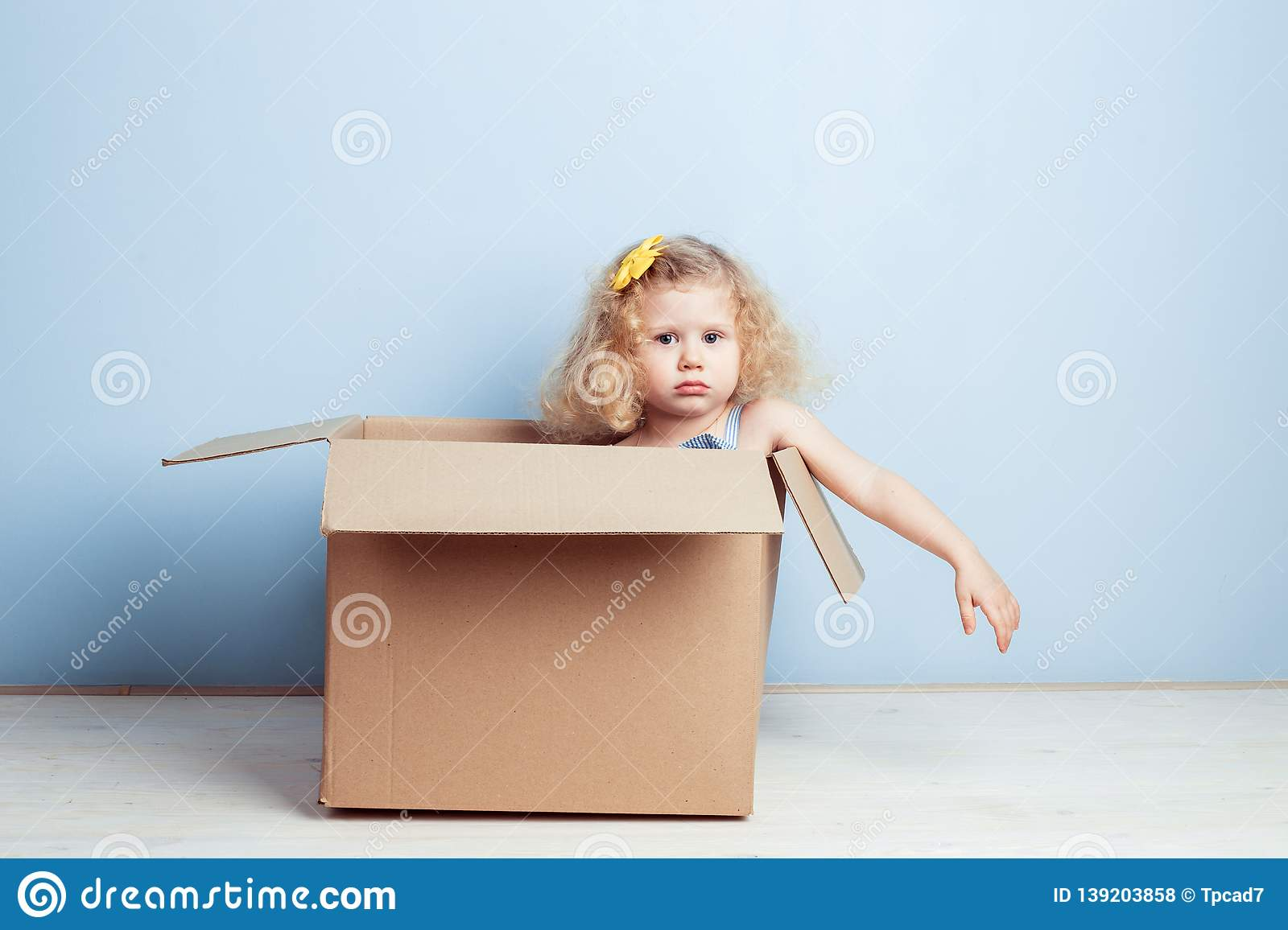 Funny little curly girl with yellow flower on her hair sits in the cardboard box on the background of blue wall.