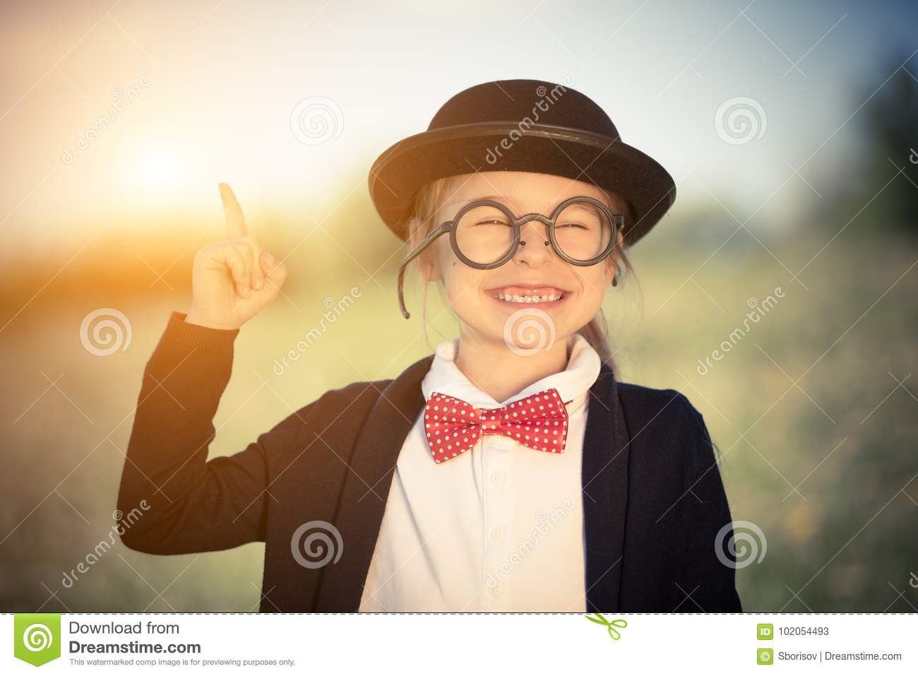 5f0ff339c44d Outdoor portrait of funny little girl in glasses, bow tie and bowler hat  pointing finger up. Retro stile.