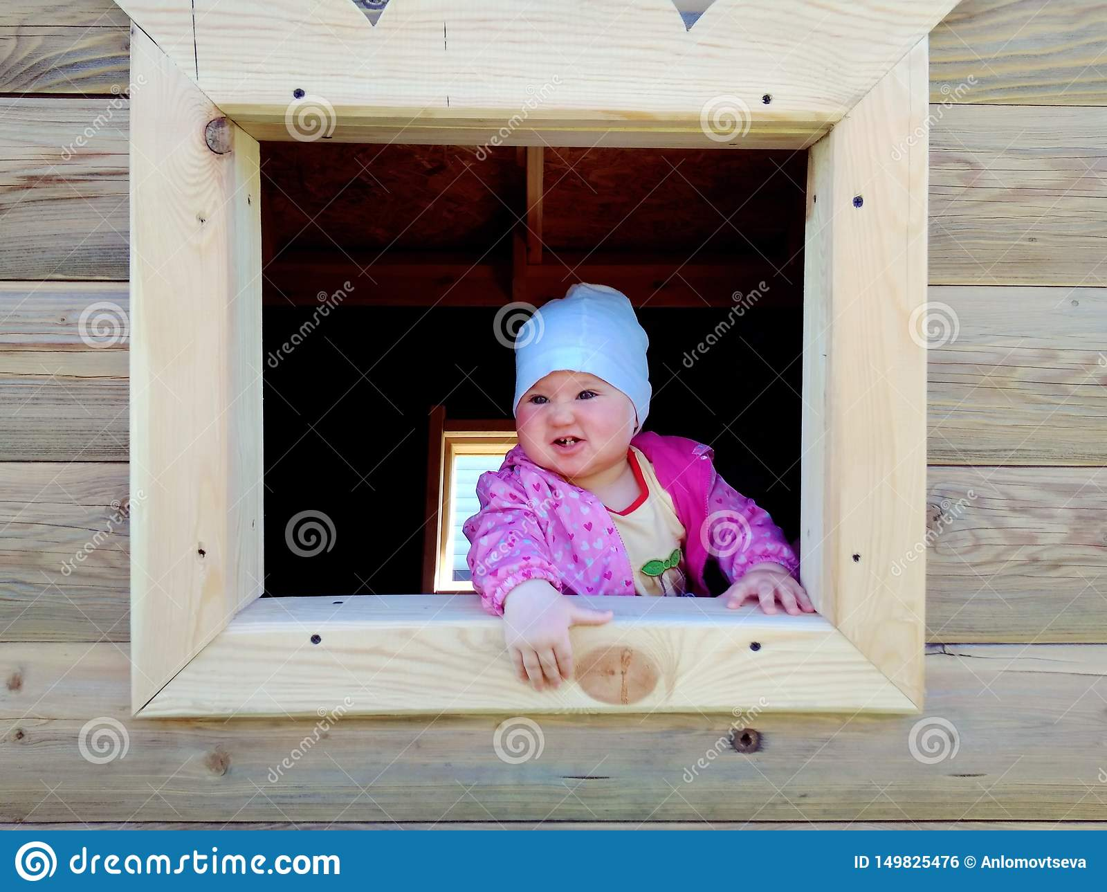 Baby playing in a wooden house