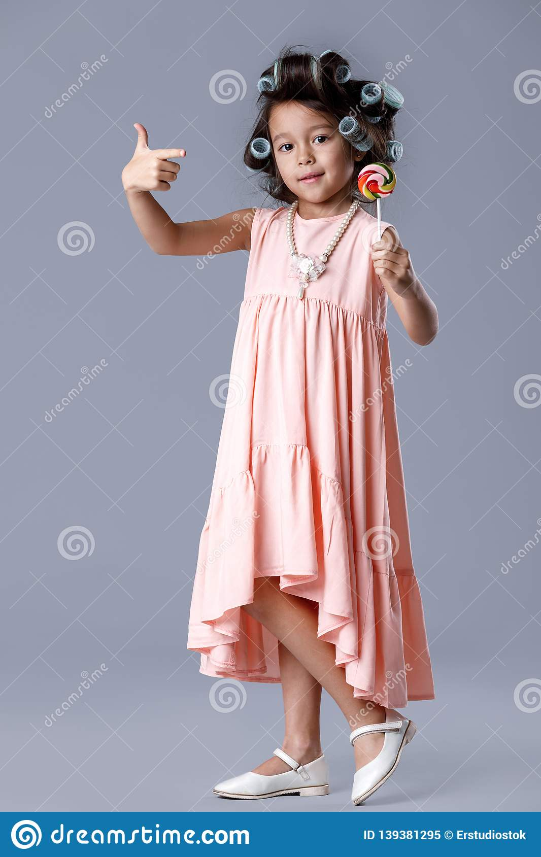 8a5bd9b55 Funny little child girl in pink dress and hair curlers pointing lollipop on  gray background.