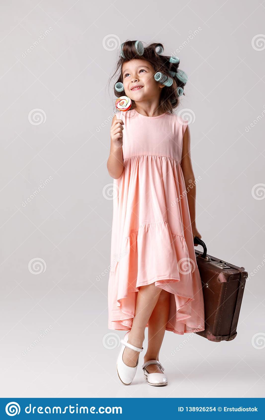 2e6102c85 Funny Little Girl In Pink Dress And Hair Curlers Holding Lollipop ...