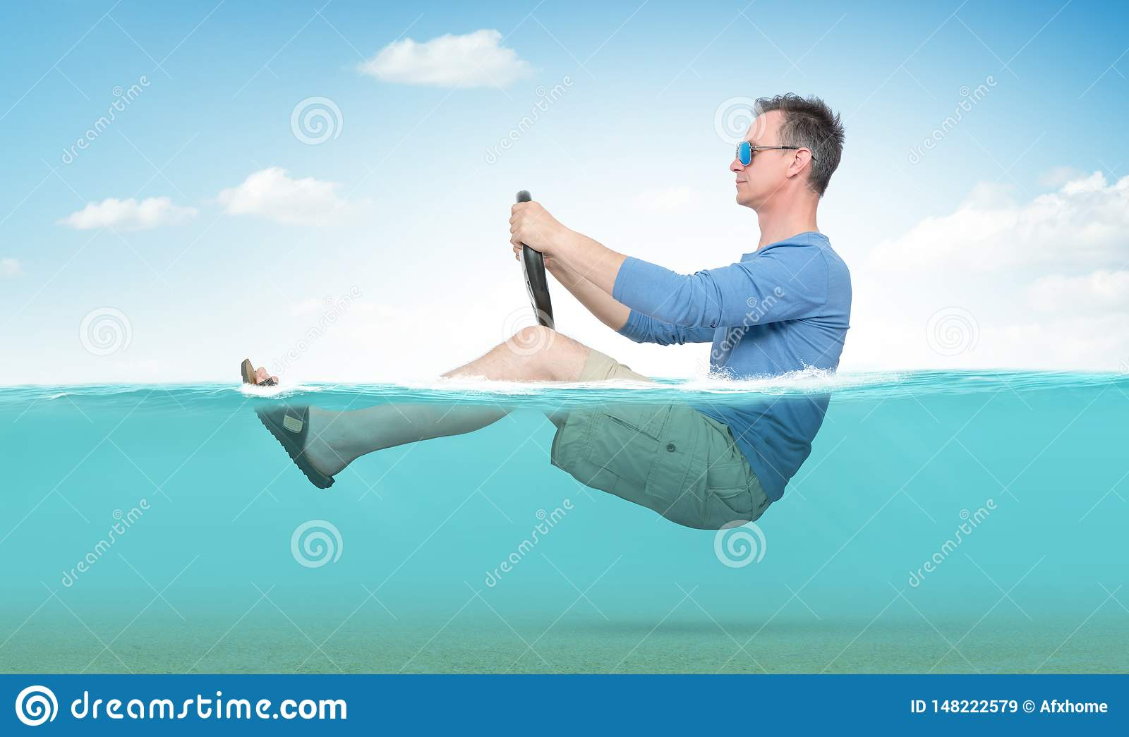 Funny man in sunglasses, shorts, T-shirt and sandals rides on the sea with a car steering wheel. Concept of going on vacation