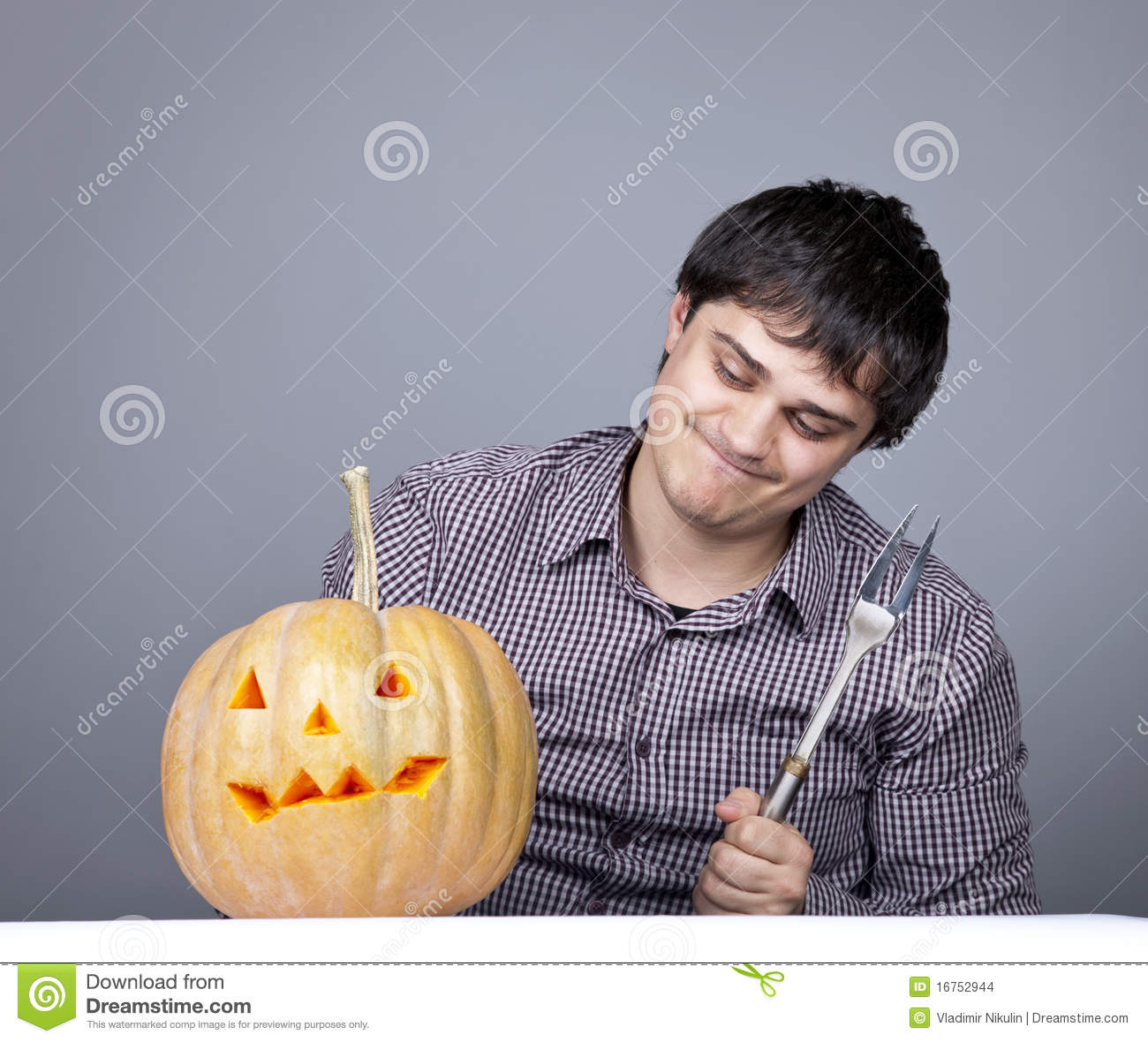 Funny men with fork try to eat a pumpkin.