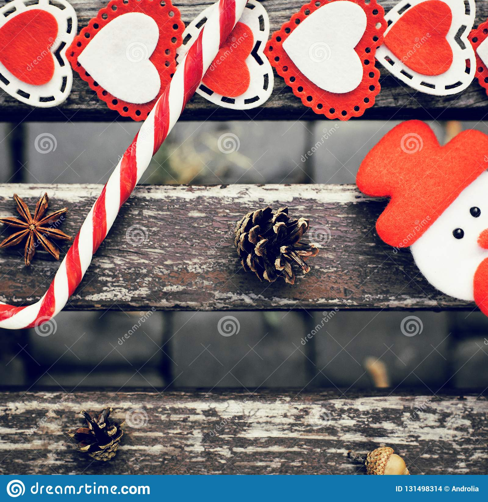 Funny outdoor Christmas composition with pine cones, lollipop, acorn, star anise, snowman and colorful felt hearts on an old