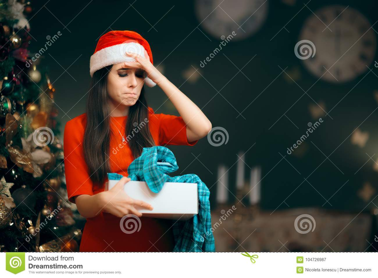 Upset Girl Opening A Bad Christmas Gift Finding Pajamas Inside Stock ...