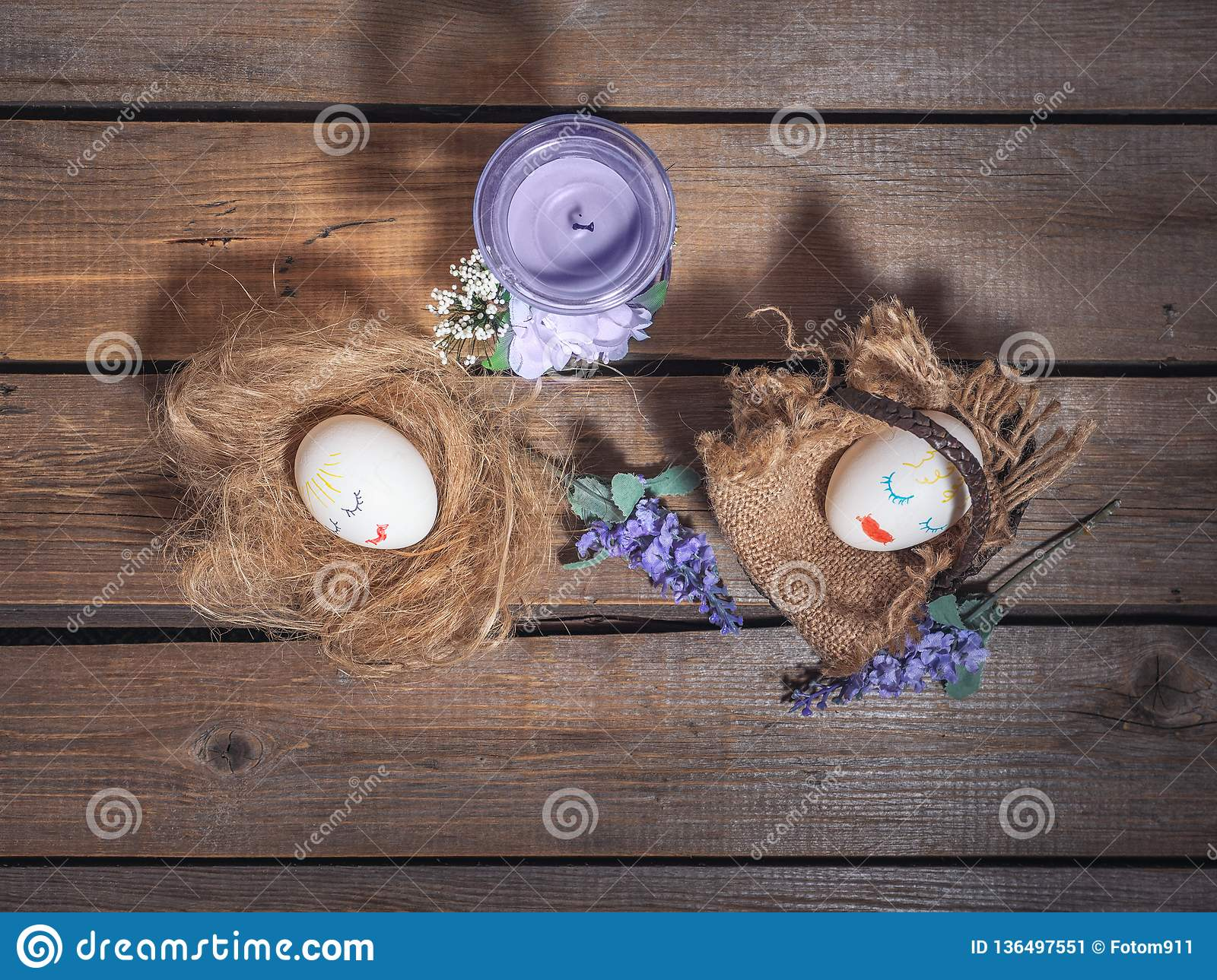 Funny picture for Easter. Eggs with painted faces. Basket and straw, next are sprigs of flowers on a wooden background