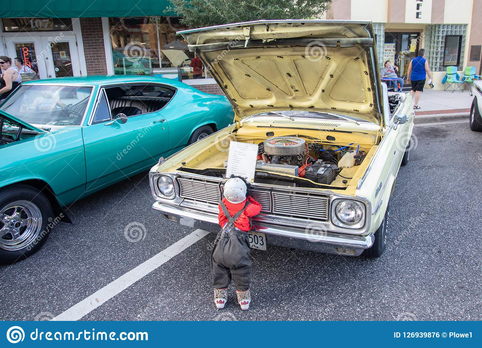 Funny Picture Of Small Doll Looking At Classic Car Editorial Photo