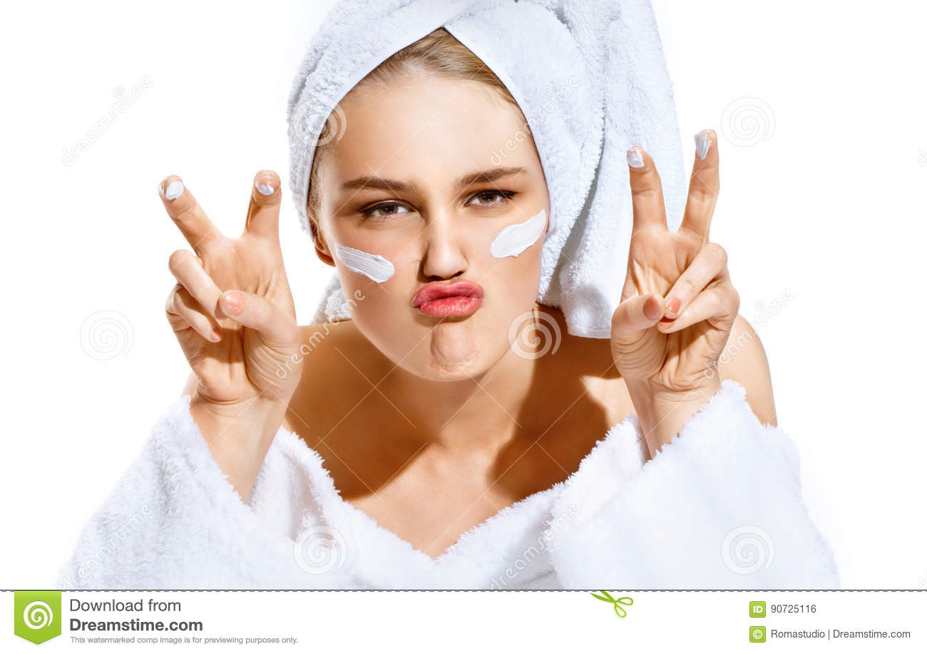 Funny playful young woman in white bathrobe applying moisturizer and making duck face over white background.