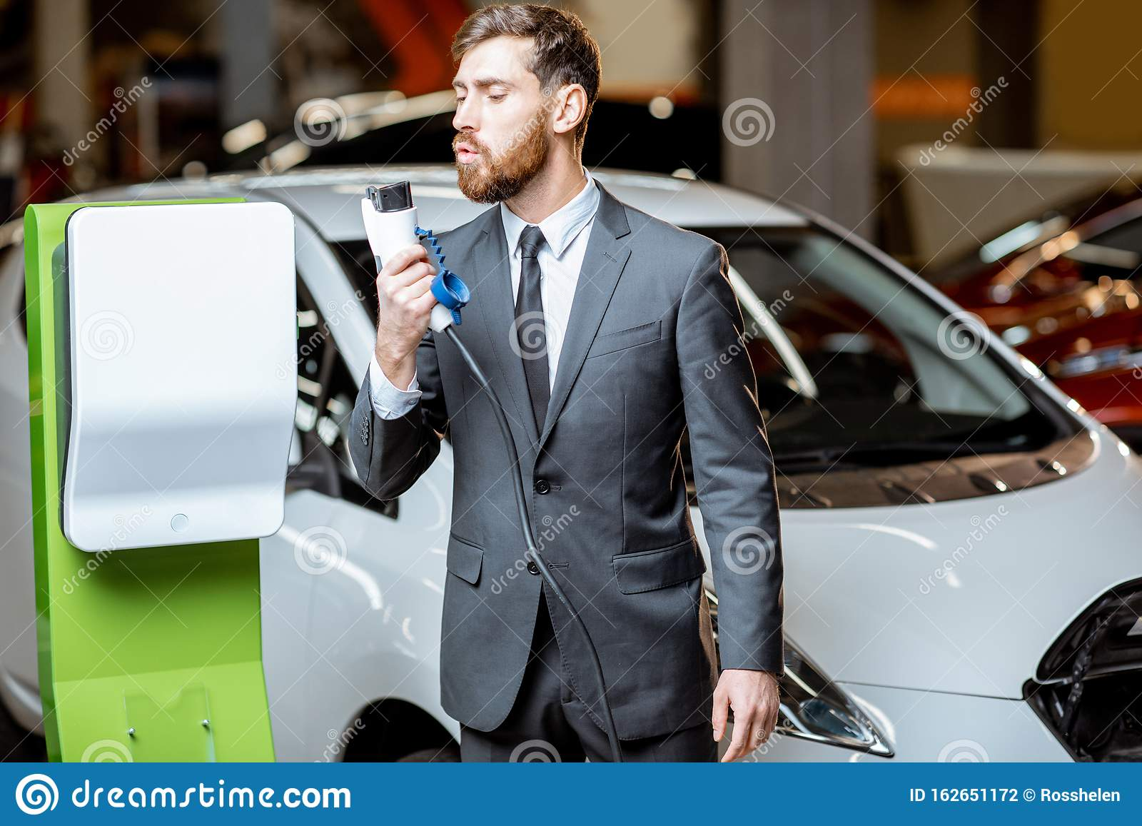 Salesman With Electric Car Charging Station In The Dealership Stock Photo Image Of Power Agent 162651172
