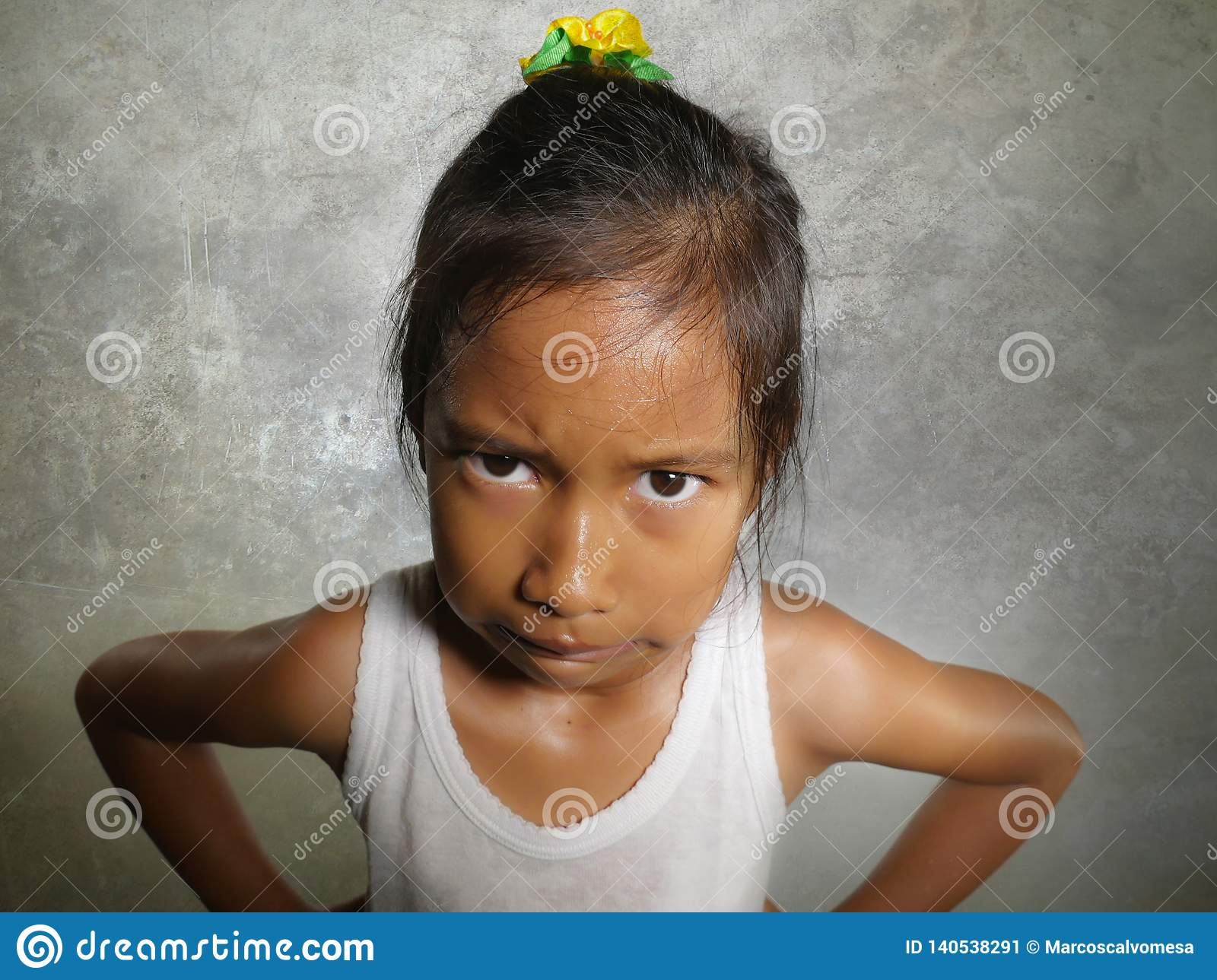 Funny portrait of sweet angry and mad 8 or 9 years old child looking upset to the camera feeling and unhappy isolated on