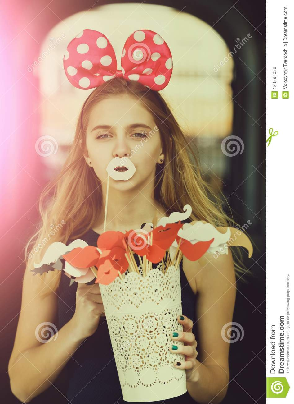 Decorative props on sticks. Funny pretty girl or young woman, teenager, with long, blond hair posing with cute mouse ears and paper white lips.