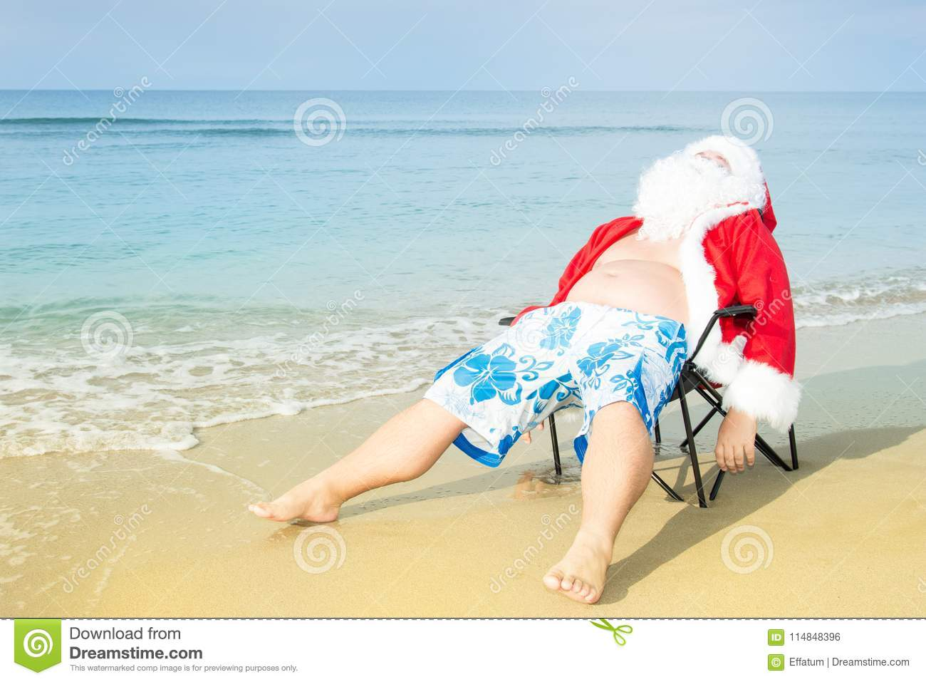Funny Santa in shorts on the beach. Christmas in the tropics.