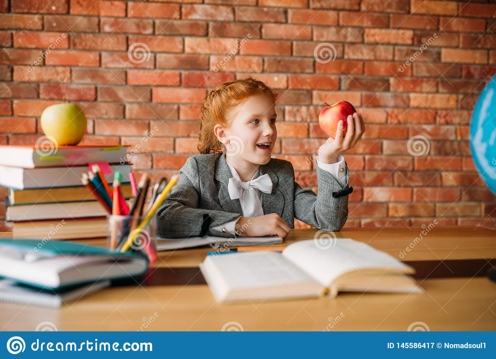 Funny schoolgirl with apple sitting at the table