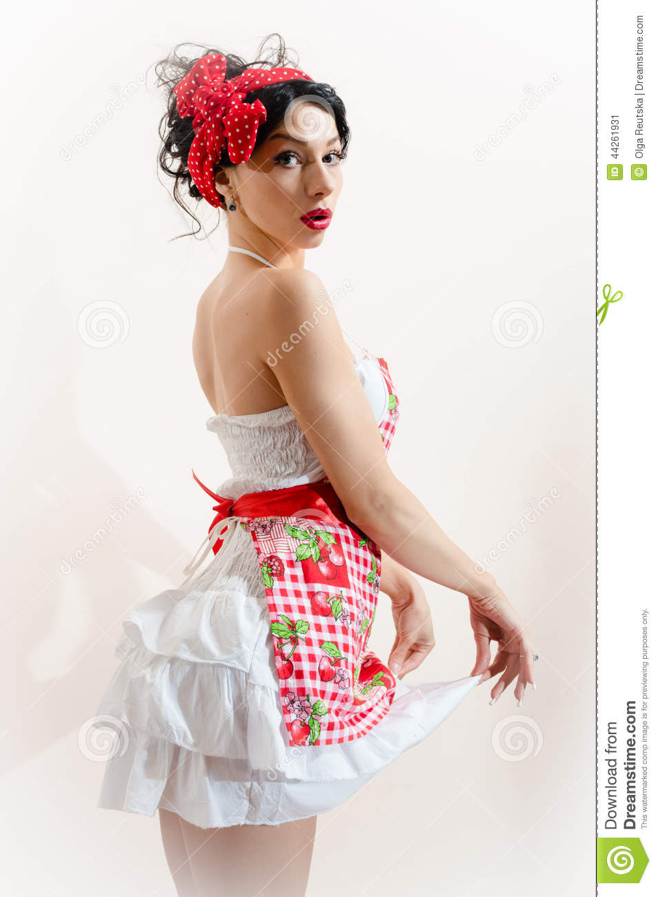 Funny young brunette pinup pretty lady with blue eyes having fun posing & looking at camera over naked shoulder