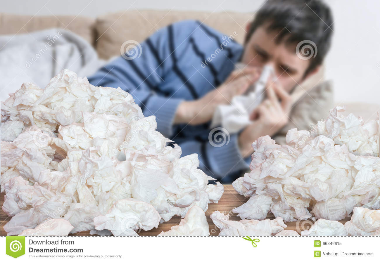 Funny sick man who has flu or cold is blowing his nose.