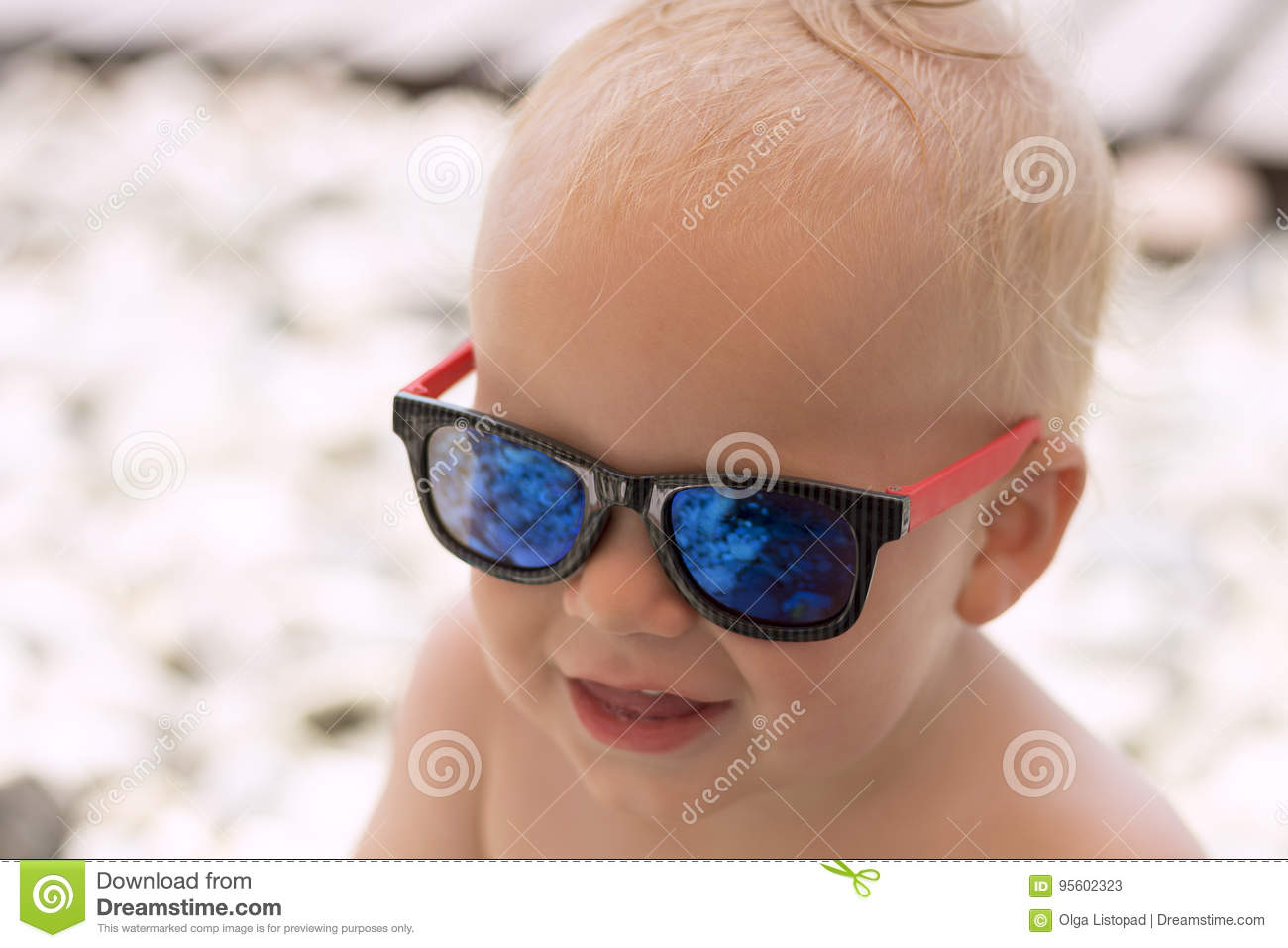 1fcf34e82e5e6 Funny smiling baby boy in sunglasses on the beach. Stones are reflected in  the glasses. Little boss on vacation.