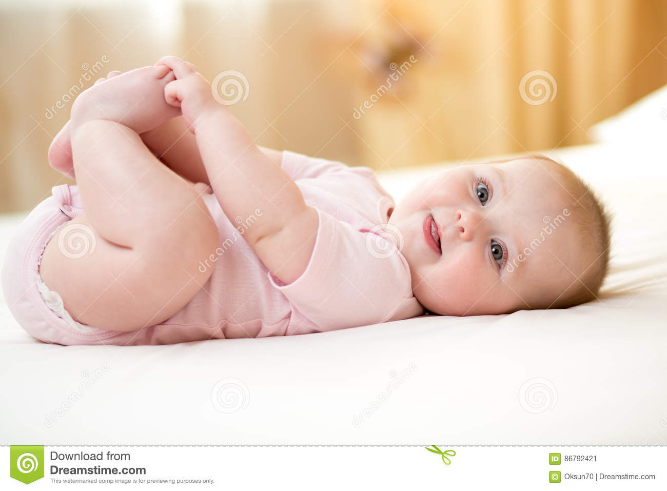 Funny Smiling Baby Infant Girl Playing With Her Feet Stock