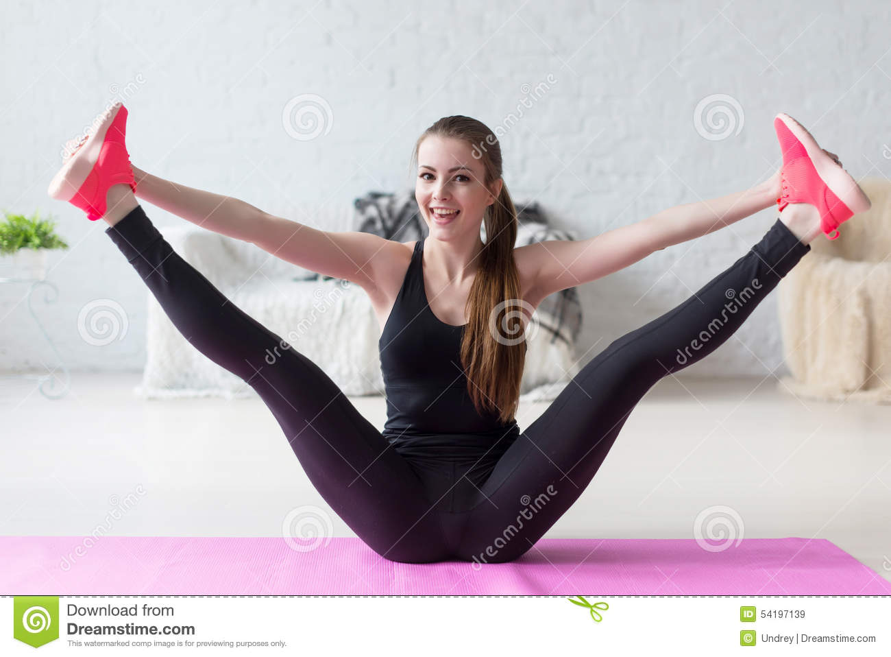Funny smiling girl holding legs apart doing exercises aerobics warming ...