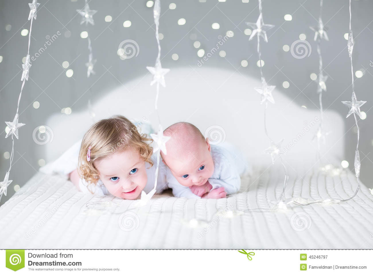 Funny toddler girl and her newborn baby brother relaxing together