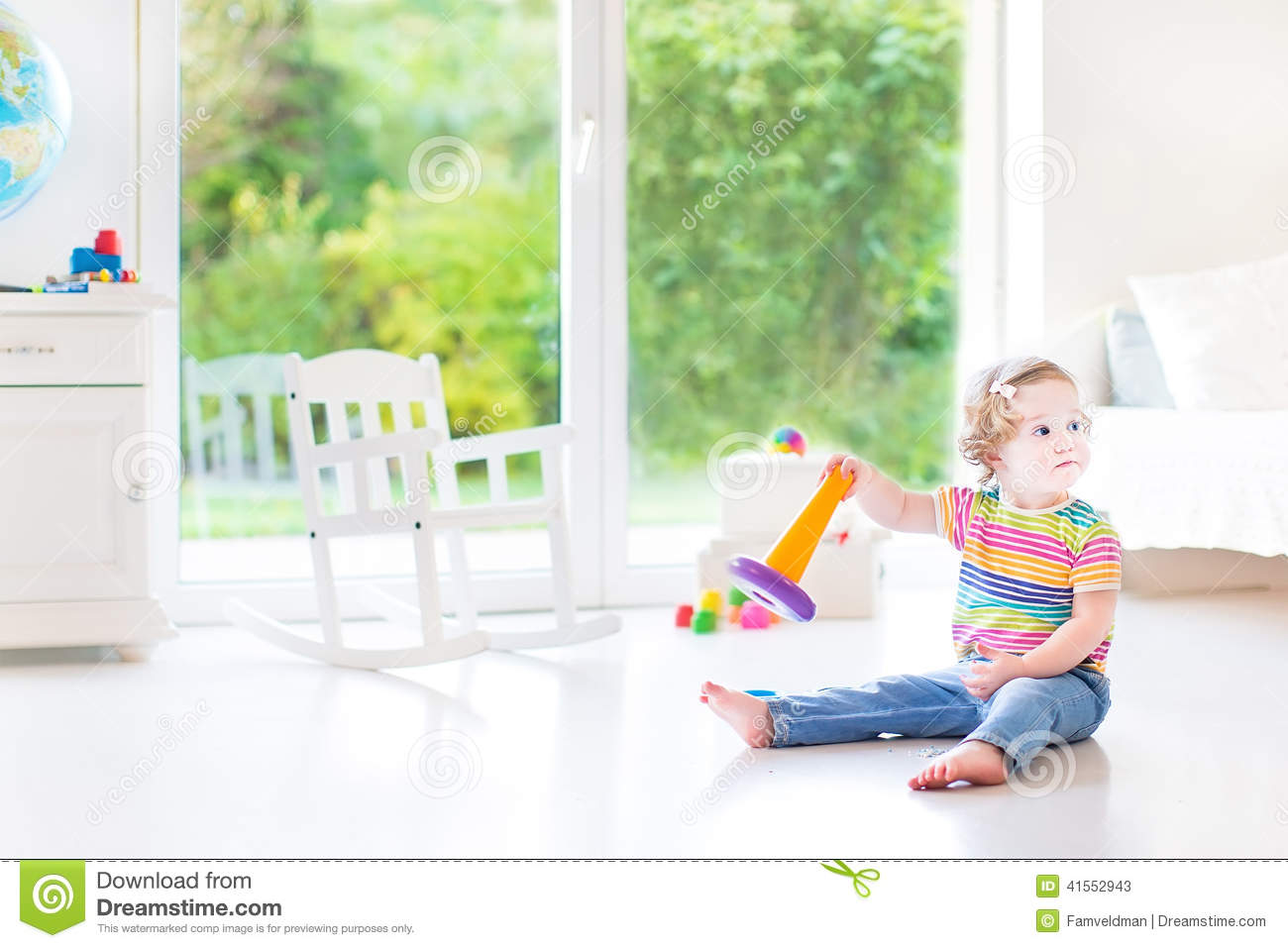 Funny toddler girl with pyramid toy in white room