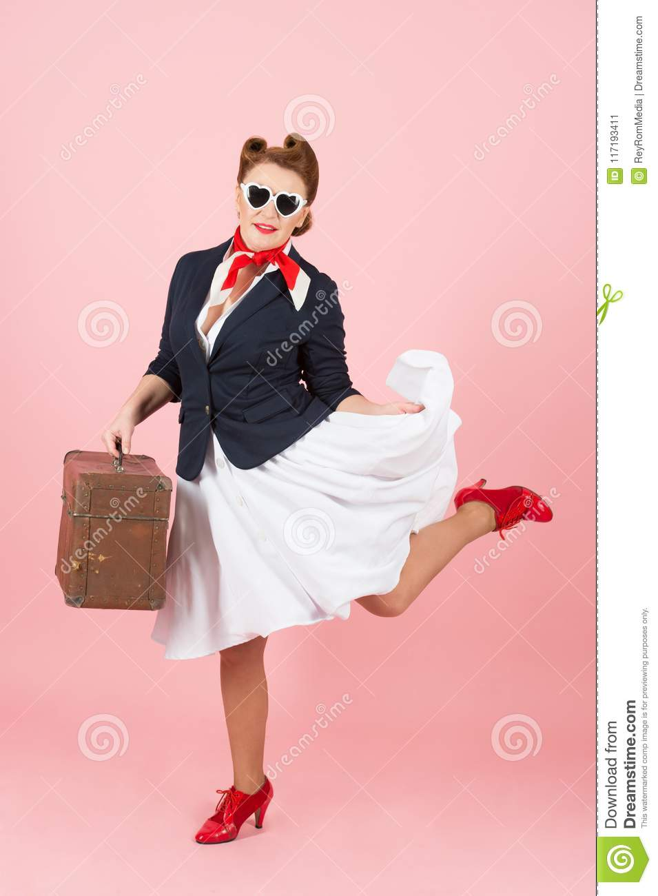 Funny traveler girl with suitcase and black sunglasses. Brunette woman in pin-up style with vintage case.